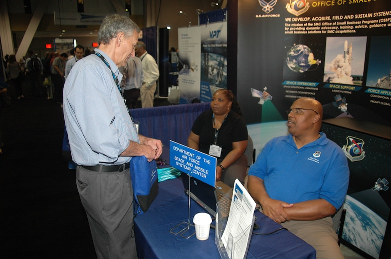 Willard Strozier, director, and Audrey Campbell, deputy director, of the Office of Small Business Programs from Space and Missile Systems Center at Los Angeles Air Force Base in El Segundo, Calif., talk with an attendee at the 2015 Space Tech Conference and Expo held at the Long Beach Convention Center May 19-21. More than 3,500 registered attendees and 200 exhibitors, including SMC participated in the three-day event. (U.S. Air Force photo/Jim Spellman)