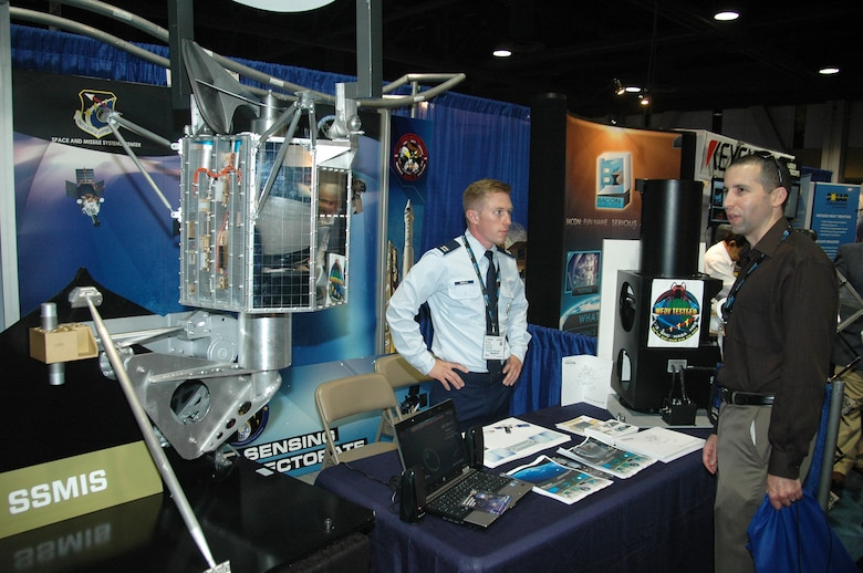 Capt. Philip Duddles, Remote Sensing Program Manager, from the Space and Missile Systems Center at Los Angeles Air Force Base in El Segundo, Calif., converses with an attendee at the 2015 Space Tech Conference and Expo at the Long Beach Convention Center May 19. More than 3,500 registered attendees and 200 exhibitors including SMC attended the three-day event. (U.S. Air Force photo / Jim Spellman)