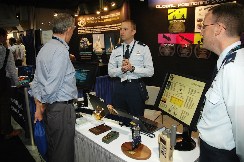 Capt. Thomas Chiasson, GPS Operational Control Systems, and Lt. Col. Jacob Freeman, GPS Deputy Chief Engineer, from the Space and Missile Systems Center at Los Angeles Air Force Base in El Segundo, Calif., talk with an attendee during the 2015 Space Tech Conference and Expo, held at the Long Beach Convention Center May 19-21. More than 3,500 registered attendees and 200 exhibitors including SMC participated in the three-day space technology event. (U.S. Air Force photo/Jim Spellman)