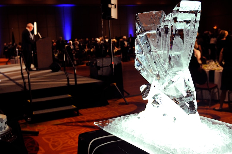Dave Webber, 55th Wing Birthday Ball master of ceremonies, speaks next to the events ice sculpture inside the Embassy Suites ballroom in La Vista, Nebraska for the 2015 Birthday Ball, May 16. The Birthday Ball is a formal celebration recognizing the wing's proud heritage as well as its current mission and role in the U.S. Air Force. (U.S. Air Force photo by Jeff W. Gates/Released)