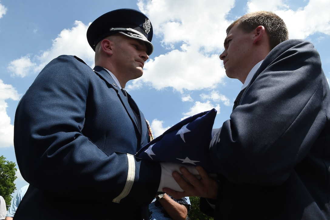 Air Force Maj. Ryan Vanveelen, U.S. Air Force Honor Guard director of operations, passes off a folded flag to Army Maj. Steven Curtis, North Carolina Defense Congressional fellow, following a ceremony in honor of Capt. Glenn Cook in front of the Vietnam Veteran's Memorial, in Washington D.C., May 19, 2015. Cook's plane was shot down near Nha Trang, Vietnam, Oct. 21, 1969. His remains were never found. (U.S. Air Force photo/Senior Airman Joshua R. M. Dewberry)