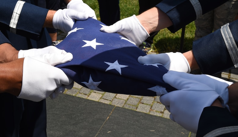 U.S. Air Force Honor Guardsmen hold a flag during flag folding ceremony in honor of Capt. Glenn Cook in front of the Vietnam Veteran's Memorial in Washington, D.C., May 19, 2015. Cook's plane was shot down near Nha Trang, Vietnam, Oct. 21, 1969. His remains were never found. (U.S. Air Force photo/Senior Airman Joshua R. M. Dewberry)