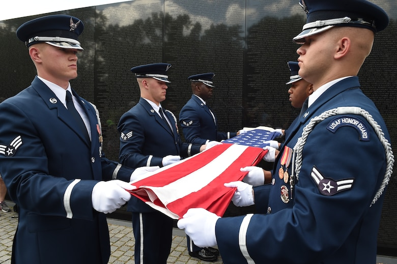 U.S. Air Force Honor Guardsmen perform a flag folding ceremony in honor of Capt. Glenn Cook, in front of the Vietnam Veteran's Memorial in Washington, D.C., May 19, 2015. Cook's plane was shot down near Nha Trang, Vietnam, Oct. 21, 1969. His remains were never found. (U.S. Air Force photo/Senior Airman Joshua R. M. Dewberry)