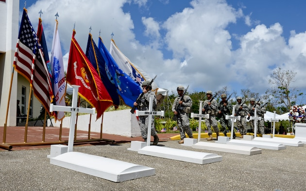 Members from the Guam National Guard, U.S. Air Force Reserves and Vietnam Veterans of America Chapter 668 perform a gravesite tribute May 25, 2015, during a Memorial Day ceremony at the Guam Veterans Cemetery in Piti. Members from each branch of service and government organizations worked together to honor the sacrifices made by all U.S. veterans, past and present. (U.S. Air Force photo by Staff Sgt. Robert Hicks/Released)