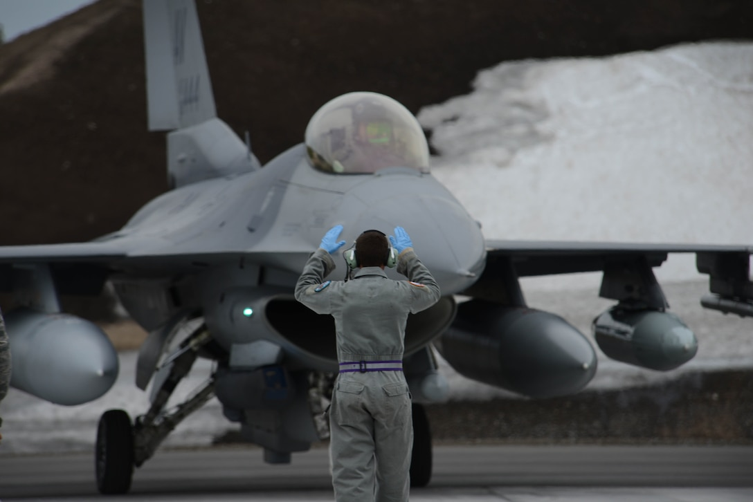 An Airman with the 510th Fighter Squadron from Aviano Air Base, Italy, guides an F-16 Fighting Falcon at Kallax Air Base, Sweden, May 22, 2015. The 510th FS took part in Arctic Challenge Exercise 2015. Nine nations also participated during the exercise to help ensure interoperability, and strengthen relationships and engagements with NATO allies and Partners for Peace. (U.S. Air Force photo/Staff Sgt. Evelyn Chavez)
