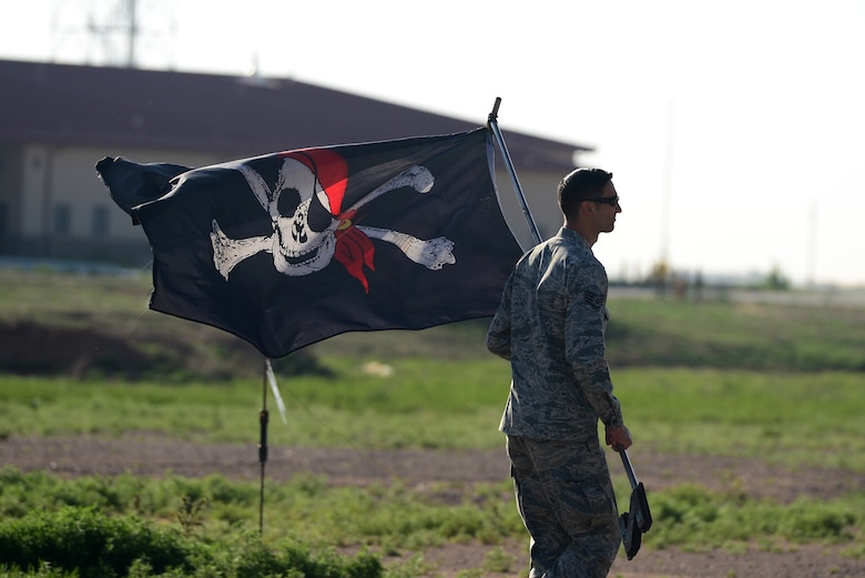 "U.S. Air Force Staff Sgt. Samuel Pearson, 27th Special Operations Aircraft Maintenance Squadron maintenance training instructor, carries the ""Jolly Roger"" flag to the AC-130H Spectre gunship, nicknamed ""Excalibur"", May 27, 2015 at Cannon Air Force Base, N.M. The ""Jolly Roger"" is a pirate flag flown to boost morale and was displayed during the final Spectre gunship deployment. (U.S. Air Force photo/Senior Airman Eboni Reece)"