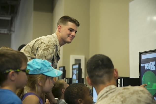 Lance Cpl. Mason Bennet, tank gunner, 1st Tank Battalion, helps students of Palm Vista Elementary School use the Advanced Gunnery Training System at the 1st Tanks Tank Ramp, May 18, 2015. The simulator allowed the children to get a glimpse of how the Marines train to operate tanks. (Official Marine Corps photo by Lance Cpl. Thomas Mudd/ Released)