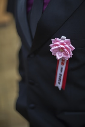 Each representative at the Meiji Jingu Gathering Hall in Tokyo, Japan, receives a ribbon from the Japan Good Deeds Association identifying that they are there to receive an award during the ceremony, May 23, 2015. The Good Deeds Association is an organization that recognizes people or groups for they're good conduct in support of the Japanese community. The association recognized service members with Headquarters and Headquarters Squadron and Marine Aerial Transport Refueler Squadron 152 aboard Marine Corps Air Station Iwakuni, Japan, for their assistance with the Iwakuni City Volunteer Council in August 2014, after a mudslide caused by heavy rain.