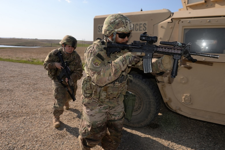 Senior Airman Rapheal Dexter, of the 91st Missile Security Forces Squadron, right, leads Staff Sgt. Shareen Mendiola, of the 219th Security Forces Squadron, as they advance on simulated intruders while utilizing a High Mobility Multipurpose Wheeled Vehicle (HMMWV), commonly known as a Humvee, for cover during a training exercise at a Minot Air Force Base, North Dakota, launch facility during a training exercise May 20, 2015. The exercise included an intermingled combination of North Dakota Air National Guard members doing their annual training and 91st Missile Security Forces Squadron members performing their day-to-day duties. The Air National Guard members are routinely integrated among the U.S. Air Force active duty personnel as they perform the real-World mission of missile field security in a seamless and indistinguishable manner. (U.S. Air National Guard photo by Senior Master Sgt. David H. Lipp/Released)