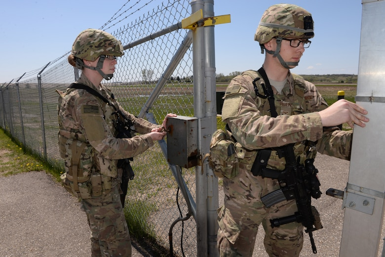 Members of the 219th Security Forces Squadron from left to right Airman 1st Class Angela Lage and Airman 1st Class Alex Pauling pass through a gate at a Minot Air Force Base, North Dakota, missile alert facility May 20, 2015, as they sweep the area for anything suspicious. The North Dakota Air National Guard members are doing their annual training period as they perform the real-World mission of missile field security, and train for their war-time tasking mission. The Air National Guard members are routinely integrated among the U.S. Air Force active duty personnel performing missile field security in a seamless and indistinguishable manner. (U.S. Air National Guard photo by Senior Master Sgt. David H. Lipp/Released)