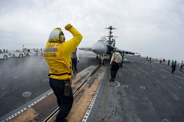 Navy Petty Officer 2nd Class Chris Gibson, left, an aviation boatswain's mate (handling), signals to the pilot of an F/A-18F Super Hornet assigned to Strike Fighter Squadron 102 on the flight deck of the aircraft carrier USS George Washington, May 19, 2015. U.S. Navy photo by Seaman Bryan Ma