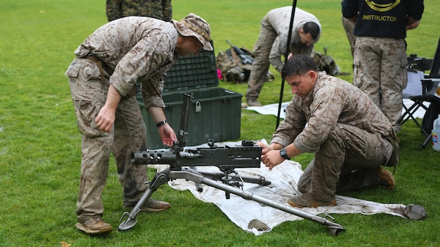 Staff Sgt. David Standridge, a reconnaissance Marine with 1st Reconnaissance Battalion, and Master Sgt. Vincent Marzi, the operations chief for 1st Force Reconnaissance Company, work as a team to assemble various weapon systems during station 5 of the 7th Annual Recon Challenge aboard Marine Corps Base Camp Pendleton, California, May 15, 2015. Competitors were tested on their knowledge as reconnaissance personnel.