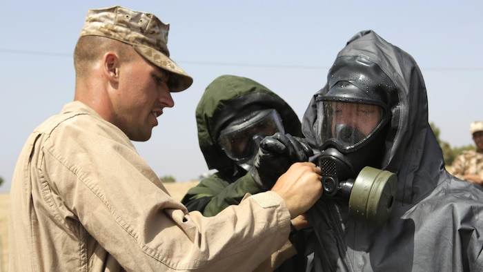 A Royal Moroccan Armed Forces soldier and U.S. Marine Corps Sgt. Brent Berven, Chemical, Biological Incident Response Force, helps Dutch 1st Soldier Peter Van Der Bourght, Netherlands Armed Forces, decontaminate his gas mask for a demonstration of Chemical, Biological, Radiological, and Nuclear defense procedures during Exercise African Lion 15 in Tifnit, Morocco, May 16. The Royal Moroccan, U.S., U.K., Netherlands, and Belgian Armed Forces integrated while conducting peacekeeping support training to improve military capabilities and operational familiarity as one international coalition.