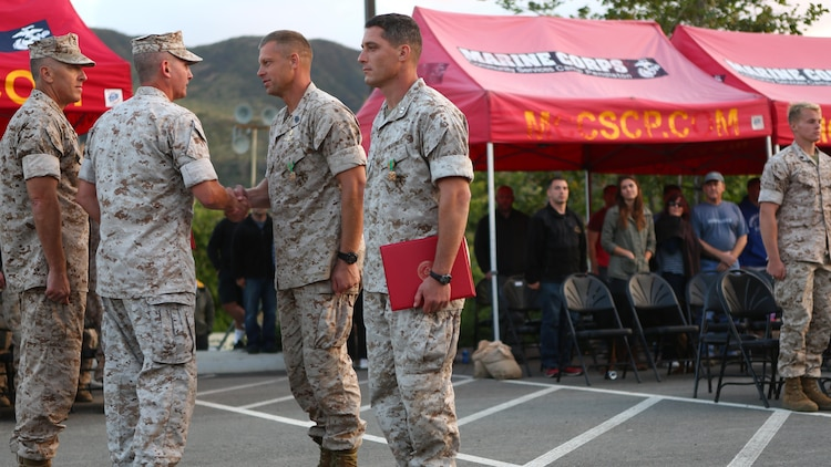 Master Sgt. David Jarvis, a reconnaissance Marine with 1st Reconnaissance Battalion, and Capt. Patrick Zuber, a company commander for 1st Reconnaissance Battalion, are awarded for winning the 7th Annual Recon Challenge aboard Marine Corps Base Camp Pendleton, California, May 15, 2015. The Marines received this honor from Col. Christopher J. Williams, the commanding officer of School of Infantry-West, and Master Gunnery Sgt. Brian Yarolem, the operations chief for Reconnaissance Training Company and event coordinator.