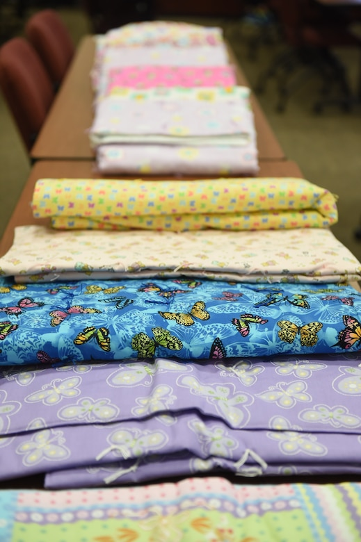 """Blankets for expecting and new parents to take home are on display during Bundles for Babies May 27, 2015, on Buckley Air Force Base, Colo. The class is offered to expecting and new parents and covers a range of topics such as car seat safety, nutrition, fitness, mental health, dividing childcare and chores, navigating common disagreements between spouses, and a family budgeting session. At the end of the class, each family gets to take home a """"bundle"""" that contains bibs, onesies, pajamas, burp towels, bath towels, crib sheets and mittens sponsored by the Air Force Aid Society. (U.S Air Force photo by Airman 1st Class Samantha Meadors/Released)"""