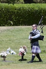 Danny Packer plays the bagpipes during a Memorial Day