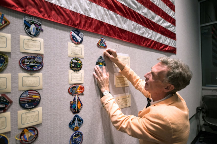 Bill Nye, Planetary Society CEO, pins a LightSail mission patch on the wall inside the Morrell Operations Center, May 21, 2015, at Cape Canaveral Air Force Station, Fla. Team Patrick-Cape hosted Bill Nye the Science Guy and the Planetary Society team for a tour of CCAFS and met with several Airmen. (Courtesy photo/Navid Baraty/Planetary Society) (For limited release)