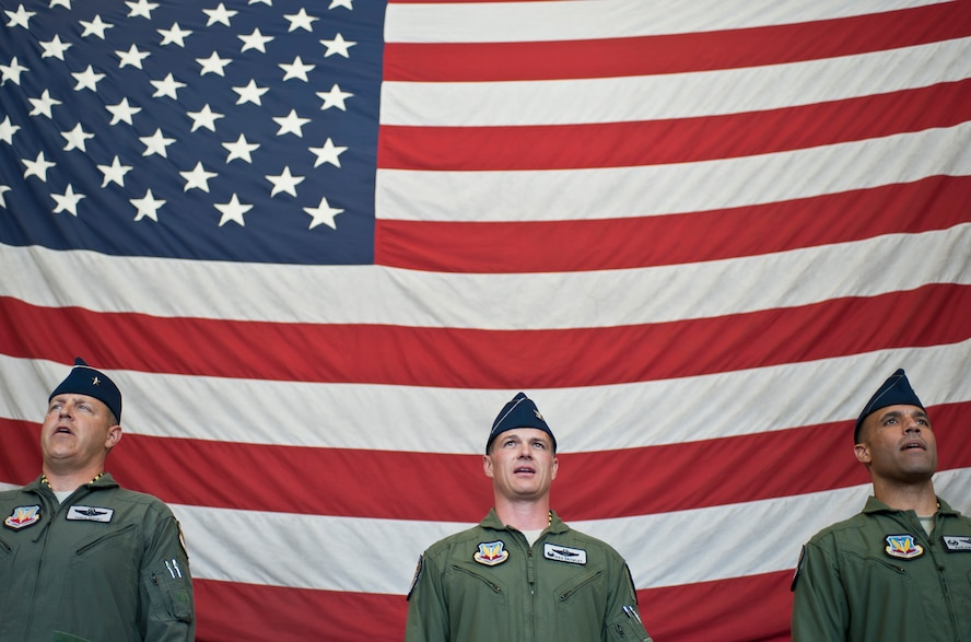 Brig. Gen. Christopher Short, Col. Michael Drowley and Col. Adrian Spain sing the Air Force song at the end of the U.S. Air Force Weapons School's change of command ceremony at Nellis Air Force Base, Nev., May 26, 2015. Short is the 57th Wing commander, Drowley is the USAFWS's commandant, and Spain is the USAFWS's former commandant. (U.S. Air Force photo by Staff Sgt. Siuta B. Ika)