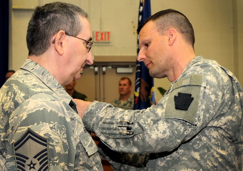 Maj. George Moebius, 56th Stryker Brigade Combat Team, 28th Infantry Division, Horsham Air Guard Station, Pennsylvania,  presents Senior Master Sgt. John Hertler of the 111th Attack Wing with the Army Commendation Medal by for his participation in Pa. Army National Guard's Vigilant Guard exercise from May 10 – 15 last year, May 21, 2015, in the wing headquarters building, Horsham AGS. The 56th SBCT is one of nine Stryker Brigade Combat Teams in the United States Army and one of five brigades of the 28th Infantry Division. (U.S. Air National Guard photo by Tech. Sgt. Andria Allmond/Released)