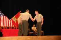 Cpl. Wesley A. Hunt, right, field artillery cannoneer, Battery A, Ground Combat Element Integrated Task Force, is congratulated by Master Sgt. James Slife III, guest speaker, during the Corporal's Course graduation at the Marine Corps Base Camp Lejeune Theater, May 28. From October 2014 to July 2015, the GCEITF conducted individual and collective level skills training in designated ground combat arms occupational specialties in order to facilitate the standards-based assessment of the physical performance of Marines in a simulated operating environment performing specific ground combat arms tasks. (U.S. Marine Corps photo by Cpl. Paul S. Martinez/Released)