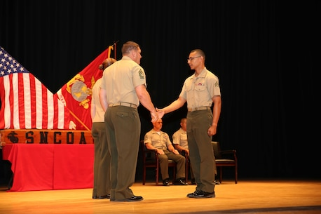 Cpl. Collin A. Bly, right, field artillery cannoneer, Battery A, Ground Combat Element Integrated Task Force, is congratulated by Master Sgt. James Slife III, guest speaker, during the Corporal's Course graduation at the Marine Corps Base Camp Lejeune Theater, May 28. From October 2014 to July 2015, the GCEITF conducted individual and collective level skills training in designated ground combat arms occupational specialties in order to facilitate the standards-based assessment of the physical performance of Marines in a simulated operating environment performing specific ground combat arms tasks. (U.S. Marine Corps photo by Cpl. Paul S. Martinez/Released)