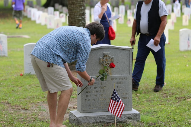A visitor at the Beaufort National Cemetery lays a rose on a veteran's grave during the annual Memorial Day Ceremony, May 25. Hundreds of veterans, active duty service members, and civilians came to pay their respects to those who laid down their lives in service to the nation.