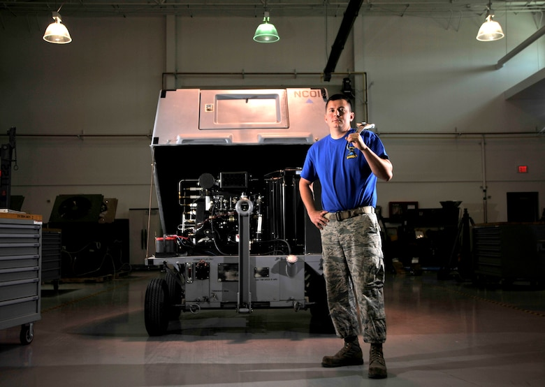 Tech Sgt. Kasey Hollinger, a 432nd Maintenance Squadron aerospace ground equipment craftsman, stands next to a self-generating nitrogen cart May 19, 2015, at Creech Air Force Base, Nev. The self-generating nitrogen cart is used to separate the nitrogen from the oxygen in the air and compresses it to be used to inflate AGE equipment and aircraft tires. (U.S. Air Force photo/Senior Airman Adarius Petty)