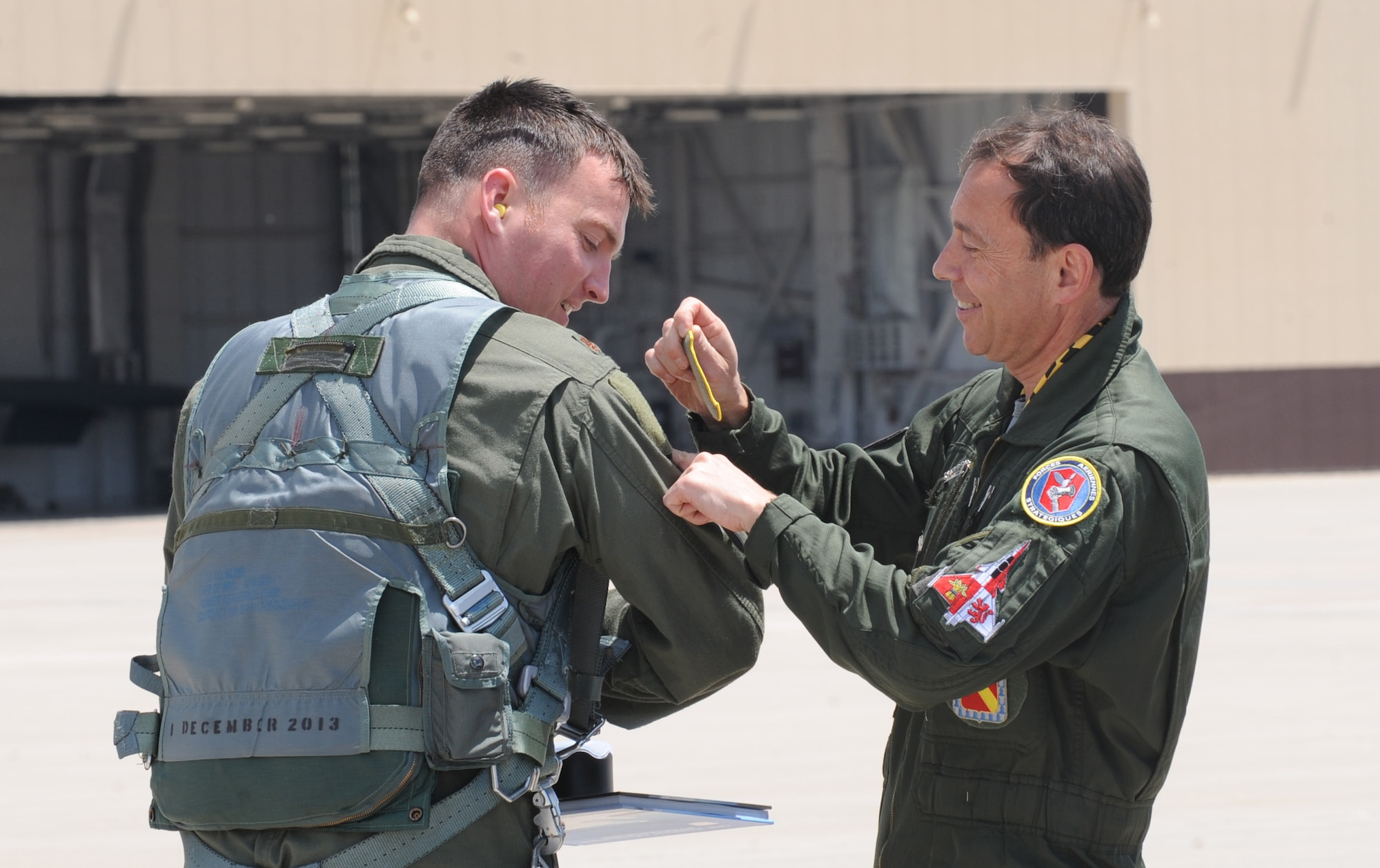 Lt. Gen. Philippe Steininger (right), the commander of the French air force's Strategic Air Forces Command, places his unit patch on Air Force Maj. Alexander Reich, a 394th Combat Training Squadron B-2 Spirit instructor pilot, at Whiteman Air Force Base, Mo., May 27, 2015. The U.S. and France have been longtime allies, joining forces in many conflicts throughout history. Steininger's visit is part of a regular series of exchanges between the two nations' strategic air forces. (U.S. Air Force photo/Staff Sgt. Alexandra M. Longfellow)