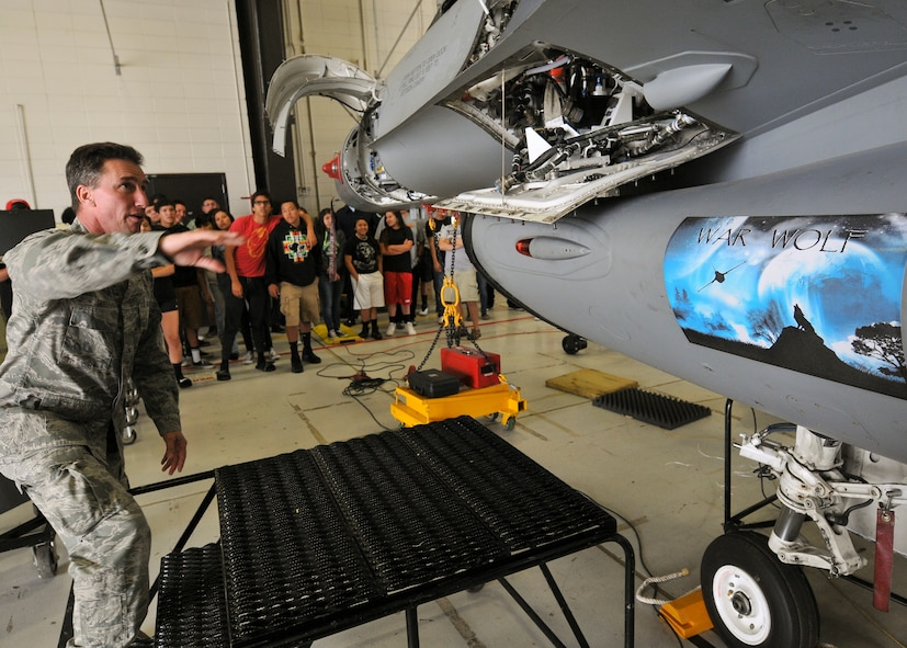 Master Sgt. Darrin Tate, 114th Aircraft Maintenance Squadron avionics technician, describes the basic functions of an F-16 Fighting Falcon to students from the Flandreau Indian School Summer Academy during a base tour of the 114th Fighter Wing in Sioux Falls, S.D., May 29, 2015. The students toured the 114th FW and were briefed about the many roles and specialized fields that make up the South Dakota Air National Guard.(National Guard photo by Staff Sgt. Luke Olson/Released)