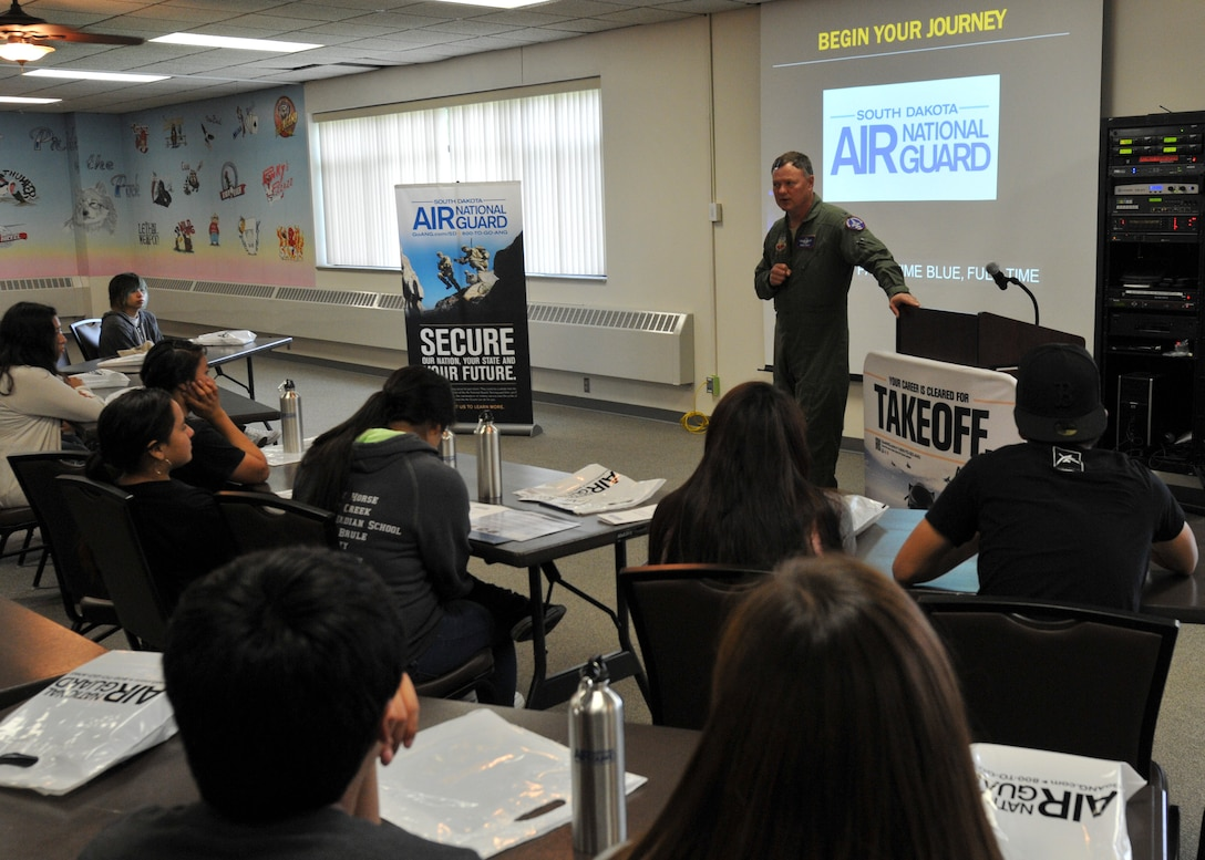Col. Russ Walz, 114th Fighter Wing commander, briefs students from the Flandreau Indian School Summer Academy about the base mission and the many roles and specialized fields that make up the South Dakota Air National Guard during a base tour at Joe Foss Field, S.D., May 29, 2015. The 114th FW hosted a base tour for 33 students and four teachers from the FIS Summer Academy to give them a closer look into the Air Force way of life. The main goal of the FIS Summer Academy is to help kids graduate early so they can begin their careers.(National Guard photo by Staff Sgt. Luke Olson/Released)