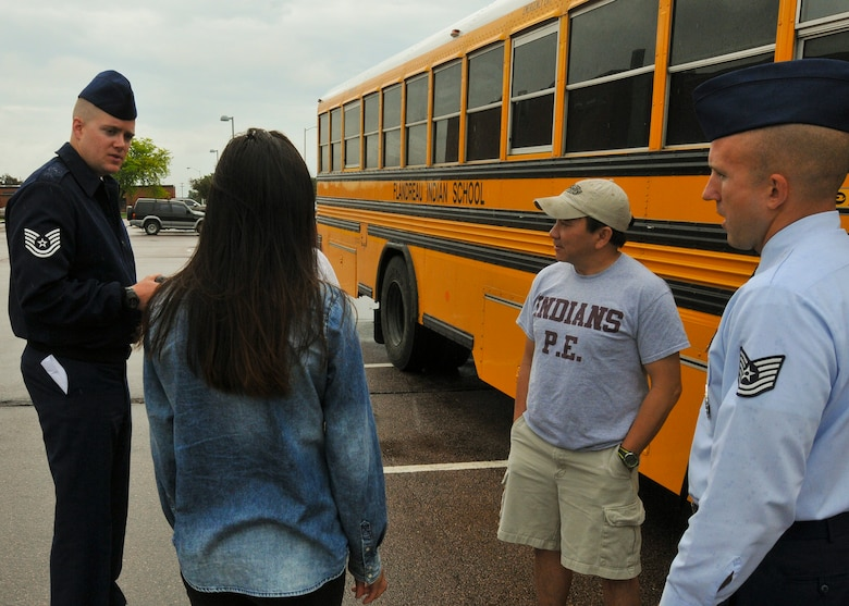 Tech Sgts. Bo Ellefson and Brian Johnson, 114th Fighter Wing recruiters, welcome students and head teacher Chi Tran from the Flandreau Indian School Summer Academy to the 114th Fighter Wing in Sioux Falls, S.D., May 29, 2015. The students toured the 114th FW and were briefed about the many roles and specialized fields that make up the South Dakota Air National Guard.(National Guard photo by Staff Sgt. Luke Olson/Released)