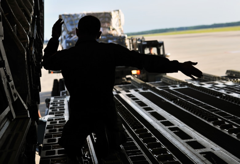 Tech. Sgt. Eric Blevins, 316th Airlift Squadron loadmaster, marshals a cargo loader toward a C-17 Globemaster, May 27, 2015, at Hurlburt Field, Fla. Members of the 823rd RED HORSE deployed to Honduras in support of NEW HORIZONS 2015, an annual event conducted to train military civil engineers and medical professionals to deploy and conduct joint operations. (U.S. Air Force photo by Airman 1st Class Ryan Conroy/Released)