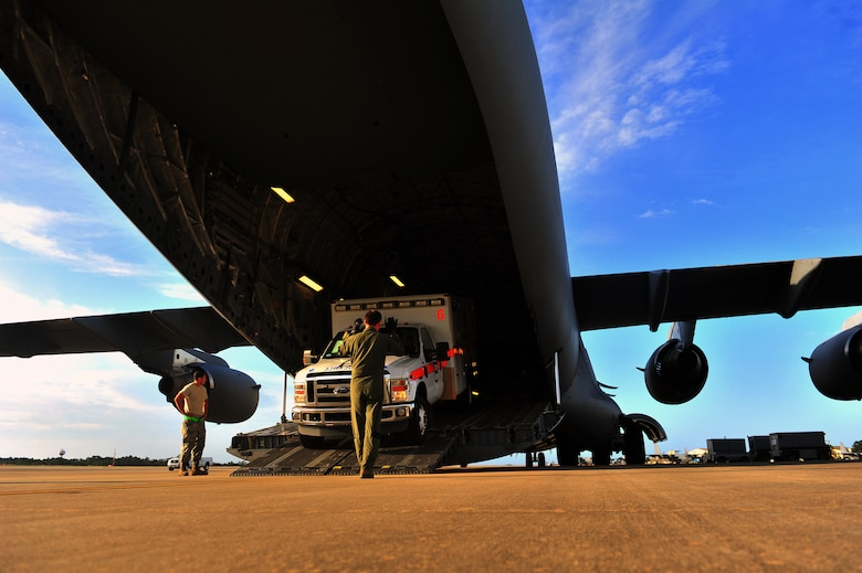 Tech. Sgt. Eric Blevins, 316th Airlift Squadron loadmaster, marshals an ambulance onto a C-17 Globemaster, May 27, 2015, at Hurlburt Field, Fla. The C-17, loaded with 823rd RED HORSE members and medical vehicles, took off in support of NEW HORIZONS 2015, an annual event conducted to train military civil engineers and medical professionals to deploy and conduct joint operations. (U.S. Air Force photo by Airman 1st Class Ryan Conroy/Released)