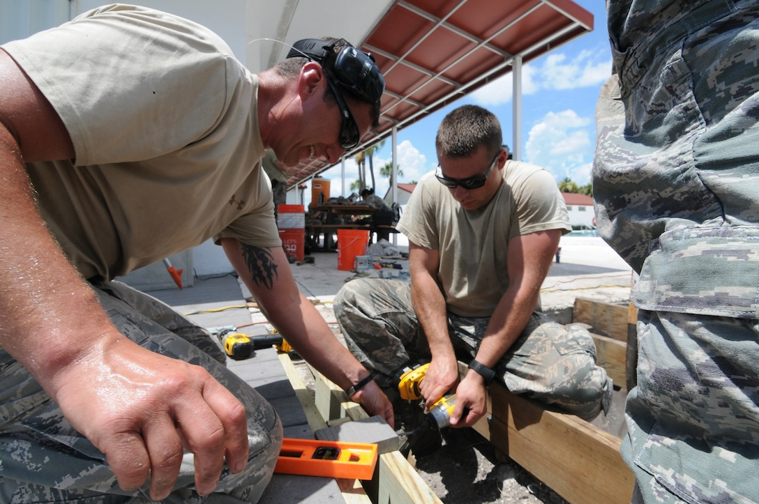 U.S. Air Force Master Sgt. Kirk Sherry, left, assists Staff Sgt. Ilya Barankevich as he drills in a screw on a new foundation that will be used for a gazebo at Coast Guard Sector St. Petersburg, Fla., on May 26, 2015. Airmen from the New Jersey Air National Guard's 177th Civil Engineering Squadron were on a deployment for training in Florida, partnering with Coast Guard Sector St. Petersburg and Air Station Clearwater. (U.S. Air National Guard photo by Airman 1st Class Amber Powell/Released)