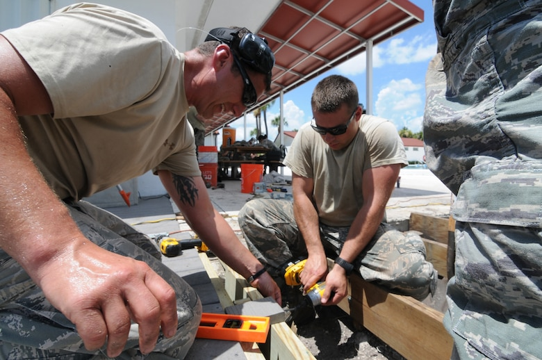 A picture of U.S. Air Force Master Sgt. Kirk Sherry assisting Staff Sgt. Ilya Barankevich as he drills in a screw on a new foundation.