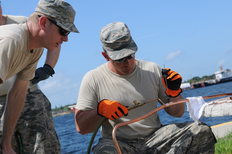 U.S. Air Force Tech. Sgt. Brian Wright, left, watches as Airman 1st Class Kristofer Flores solders two copper pipes together that will be connected to an air conditioning unit that is being installed at Coast Guard Sector St. Petersburg, Fla., on May 26, 2015. Wright and Flores, with the  New Jersey Air National Guard's 177th Civil Engineering HVAC shop, were installing an air conditioning unit that the copper pipe will be fitted to while on a deployment for training. (U.S. Air National Guard photo by Airman 1st Class Amber Powell/Released)