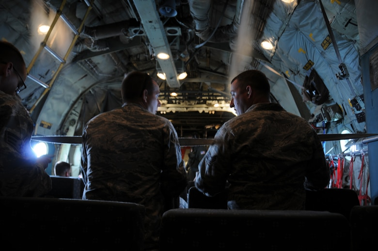 A picture of U.S. Air Force Senior Airman Michael Garcia and Senior Airman David Ringer, both from the 177th Civil Engineering Squadron, talking on a U.S. Coast Guard C-130 Hercules.