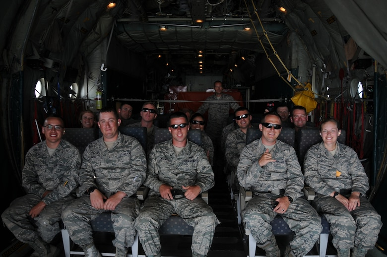 A picture of a group of Airmen looking out from a Coast Guard C-130 Hercules