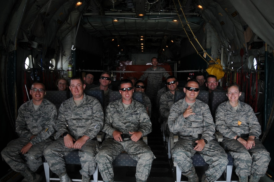 A group of Airmen from the New Jersey Air National Guard's 177th Civil Engineering Squadron, look out from a Coast Guard C-130 Hercules on May 22, 2015. Before the Memorial Day weekend the Airmen, working with Air Station Clearwater on a deployment for training, were able to tour Coast Guard Air Station Clearwater, Fla., and take a flight with the crew on a C-130. (U.S. Air National Guard photo by Airman 1st Class Amber Powell/Released)