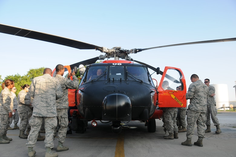 A picture of U.S. Air Force Airmen taking a look inside of an MH-60 Jayhawk helicopter.