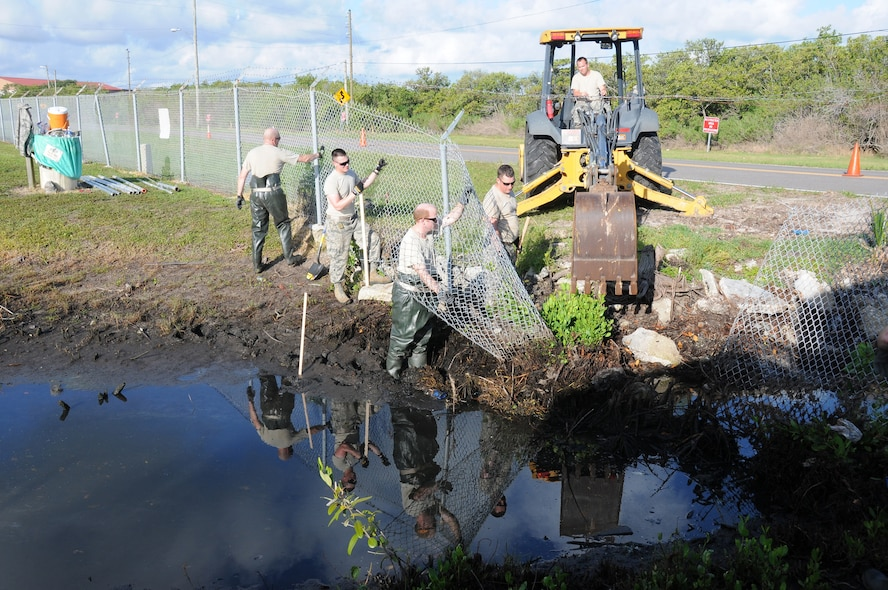 U.S. Air Force Airmen from the New Jersey Air National Guard's 177th Civil Engineering Squadron, remove a fence and clean out a drainage ditch at Coast Guard Air Station Clearwater, Fla., on  May 21, 2015. After cleaning out the area, a new fence was installed on the same day. The Airmen were on a deployment for training in Florida, partnering with Coast Guard Sector St. Petersburg and Air Station Clearwater. (U.S. Air National Guard photo by Airman 1st Class Amber Powell/Released)