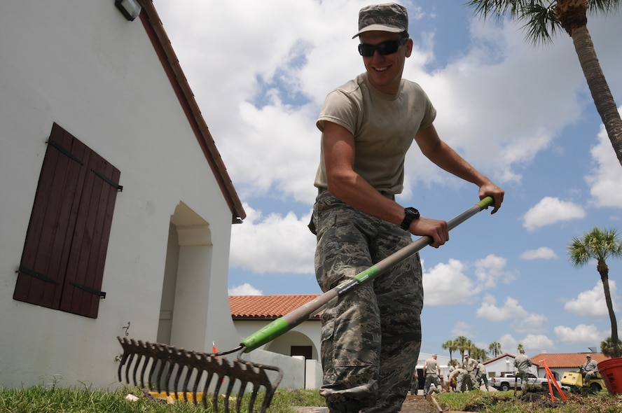 U.S. Air Force Airman 1st Class David Siligato spreads out small sea shells that will be used as foundation under a new concrete sidewalk at Coast Guard Sector St. Petersburg, Fla. on May 20, 2015. Airmen from the New Jersey Air National Guard's 177th Civil Engineering Squadron were on a deployment for training in Florida, partnering with Coast Guard Sector St. Petersburg and Air Station Clearwater. (U.S. Air National Guard photo by Airman 1st Class Amber Powell/Released)