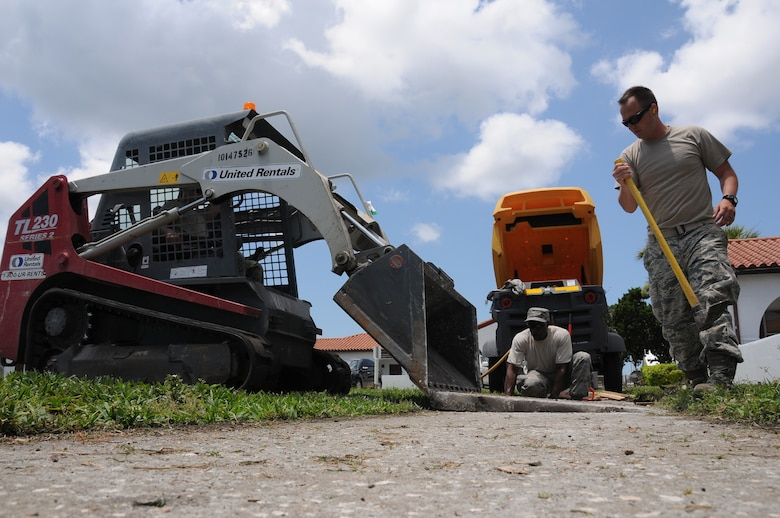 A picture of U.S. Air Force Master Sgt. Delroy Wallace and Senior Airman Michael Garcia guiding Airman 1st Class Christopher LoDico as he operates a skid steer.