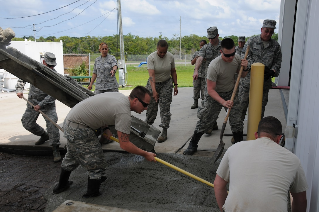 U.S. Air Force Airmen from the New Jersey Air National Guard's 177th Civil Engineering Squadron, spread out wet concrete while adding to an existing area at Coast Guard Air Station Clearwater, Fla., on May 19, 2015. They have to work quickly in order to fill the area evenly so they can smooth it out before the concrete hardens. (U.S. Air National Guard photo by Airman 1st Class Amber Powell/Released)
