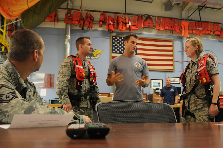 A picture of Coast Guard Petty Officer 3rd Class Spencer Caraballo, aviation survival technician, briefing U.S. Air Force Airmen from the 177th Civil Engineering Squadron.