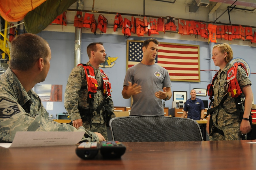 U.S. Air Force Airmen from the New Jersey Air National Guard's 177th Civil Engineering Squadron meet with Coast Guard Petty Officer 3rd Class Spencer Caraballo, aviation survival technician, for a brief on water survival equipment at Coast Guard Air Station Clearwater, Fla., on May 19, 2015. Airmen from the 177th Fighter Wing were preparing for the opportunity to assist the Coast Guard by acting as survivors during their search and rescue training. (U.S. Air National Guard photo by Airman 1st Class Amber Powell/Released)