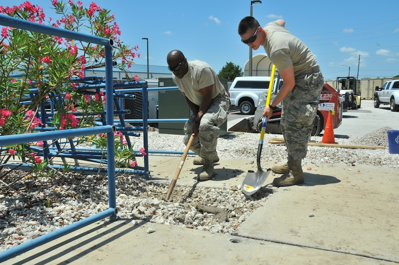 A picture of U.S. Air Force Master Sgt. Delroy Wallace and Airman 1st Class Christopher LoDico, from the 177th Civil Engineering Squadron, moving rocks before pouring concrete.