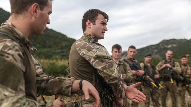 Royal Marines with 45 Commando and U.S. Marines with Special-Purpose Marine Air-Ground Task Force Crisis Response-Africa discuss tactics and techniques for patrols during Trident Juncture 15, Oct. 21, 2015. Trident Juncture is one of many exercises ensuring that NATO is ready to deal with any emerging crisis from any direction, and that the Alliance is able to work effectively with partner nations.
