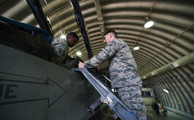 Staff Sgt. Angelo Lowe and Senior Airman James Glass, both 8th Maintenance Squadron egress systems technicians, perform an inspection on the landing gear of an F-16 Fighting falcon at Kunsan Air Base, Republic of Korea, Oct. 29, 2015.  The ejection system is a pilot's only chance at survival if all other means fail to correct an aircraft malfunction. (U.S. Air Force photo by Staff Sgt. Nick Wilson/Released)