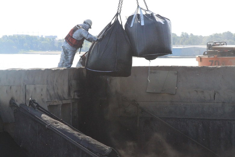 Super sacks of powdered and granular activated carbon are added to a scow of dredged sediment before mixing with a clamshell bucket.